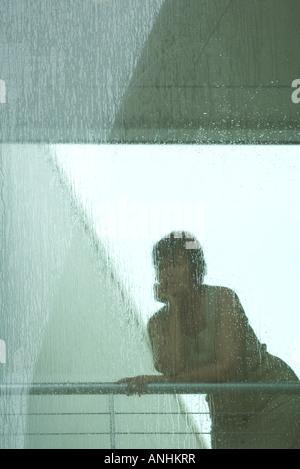 Donna che guarda attraverso la finestra in caso di pioggia Foto Stock