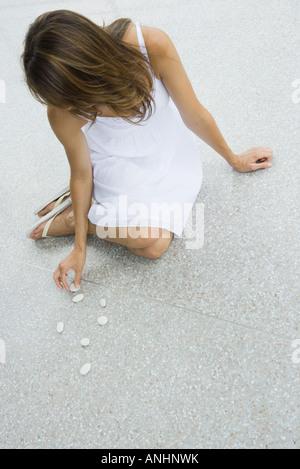 Donna seduta sul terreno disponendo ciottoli Foto Stock