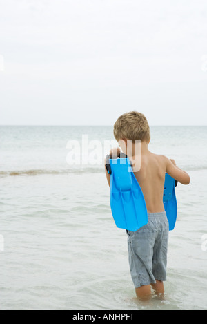 Giovane ragazzo in piedi ginocchio profondo in acqua portando, pinne, vista posteriore Foto Stock