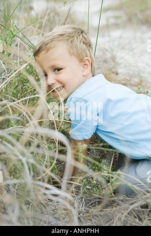 Giovane ragazzo accovacciato in erba alta, guardando sopra la spalla in telecamera Foto Stock