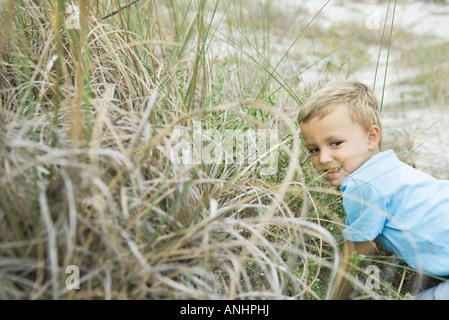 Giovane ragazzo accovacciato in erba alta, guardando lontano Foto Stock
