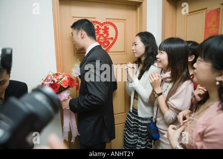 Nozze cinesi, sposo holding bouquet e a bussare alla sposa la porta mentre sposa amici guardare Foto Stock