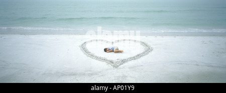 Bambino giacente all'interno del cuore disegnato sulla spiaggia Foto Stock