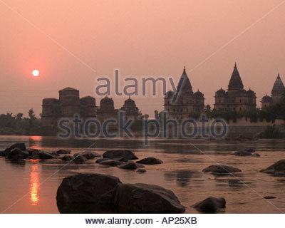 Orchha Madhya Pradesh India. Fiume Betwa al tramonto con il sole che tramonta dietro le cupole e guglie di Chhatris Foto Stock