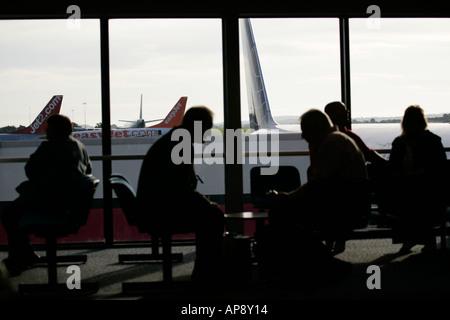 I passeggeri in attesa nella lounge nella parte anteriore della finestra a Belfast International Airport Irlanda Foto Stock