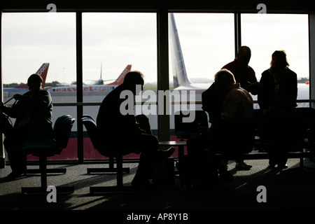 Il passeggero in attesa nella lounge nella parte anteriore della finestra a Belfast International Airport Irlanda Foto Stock