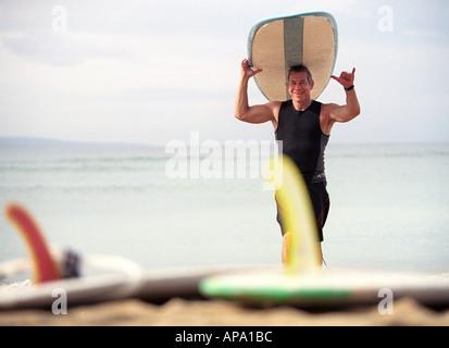 Surfista maschio gesticolando aloha come egli cammina al di fuori dell'acqua con la sua tavola da surf Foto Stock