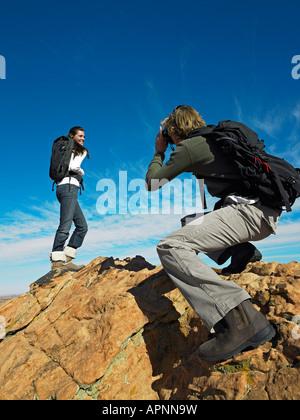 L'uomo prendendo Fotografia di donna su massi Foto Stock