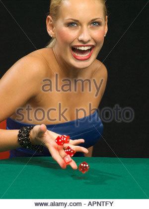 Donna felice gettando dadi Foto Stock