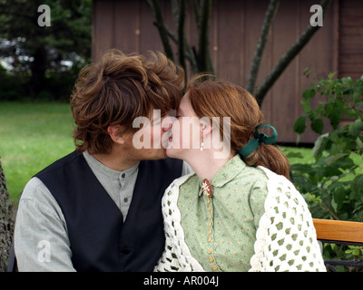 Una giovane coppia condividono un bacio in pubblico in una rievocazione storica occidentale Foto Stock