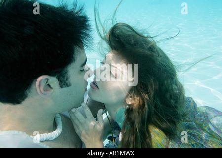 Coppia giovane circa a baciare sott'acqua. Foto Stock