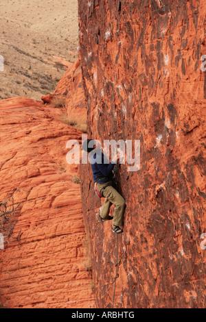 Donna asiatica scalatore di piombo si arrampica una verticale di arenaria rossa roccia Foto Stock