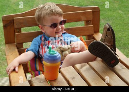 Tre anni di old boy in posa con occhiali da sole e i piedi sul tavolo Foto Stock