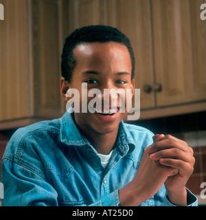 Ritratto informale all'interno del bel giovane afro-caraibica ragazzo adolescente con bretelle dentali Foto Stock