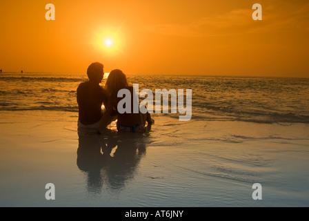 Giovane seduto alla spiaggia, stagliano al tramonto, Maldive Foto Stock