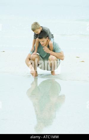 L'uomo accovacciato in spiaggia, figlio di contenimento sulle spalle, puntando al fondale basso Foto Stock