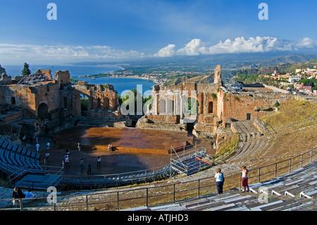 Il Teatro Greco di Taormina in Sicilia con la costa di Naxos e cloud-inghirlandato Etna in background