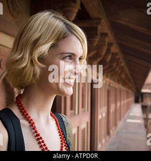 Close-up di una giovane donna sorridente e guardando lontano, Taj Mahal, Agra, Uttar Pradesh, India Foto Stock