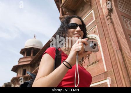 Basso angolo vista di una giovane donna in possesso di una fotocamera digitale e sorridente, Taj Mahal, Agra, Uttar Foto Stock