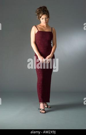 Triste timido elegantemente vestito donna in studio corpo pieno ritratto Foto Stock