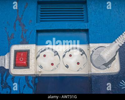 Graffiti pittura con un mulitple presa su una parete di un electrian scatola di distribuzione Foto Stock