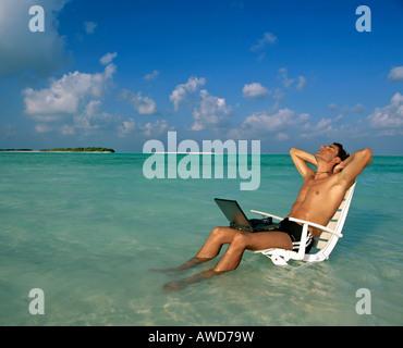 Giovane Uomo con laptop seduto sulla sedia a sdraio, il lavoro e il relax, vacanze e stress, Maldive, Oceano Indiano