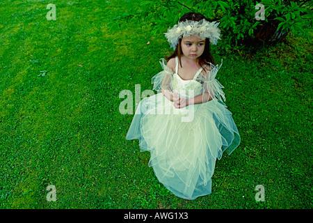 Bambina di 3 anni in una damigella abito sotto un albero su un verde prato Foto Stock