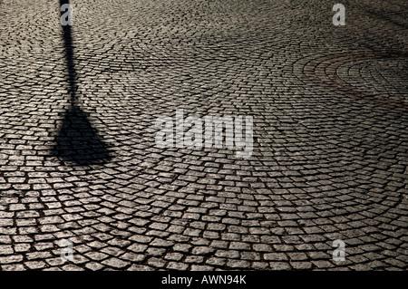 Street-lantern ombra su una strada di ciottoli, retroilluminazione Foto Stock