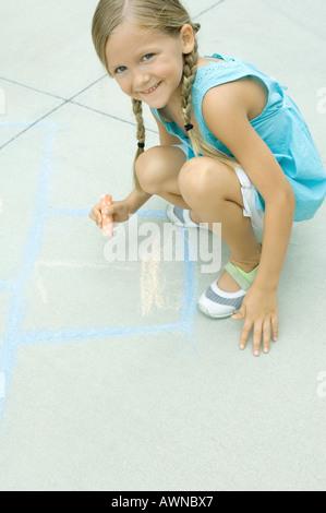 Disegno ragazza campana gioco sul viale di accesso Foto Stock