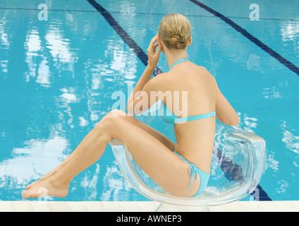 Donna in bikini seduti in piscina nella sedia trasparente Foto Stock