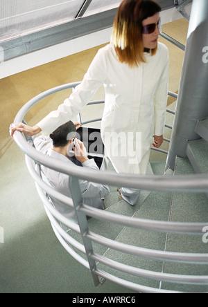 Uomo seduto sulle scale, donna venuta su per le scale, ad alto angolo di visione Foto Stock