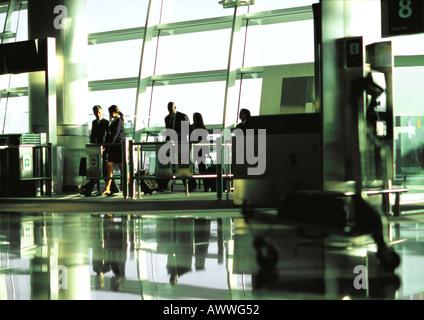 La gente di affari a piedi attraverso airport terminal gate nella distanza. Foto Stock