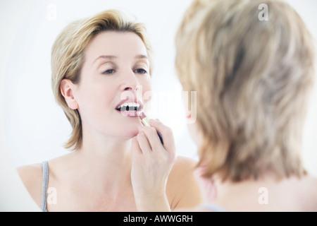 Una donna rossetto nello specchio Foto Stock