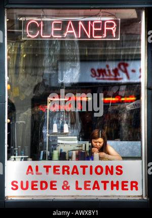 Donna in sarto Pulitore a secco Negozio finestra anteriore funziona da macchina da cucire colore verticale Foto Stock