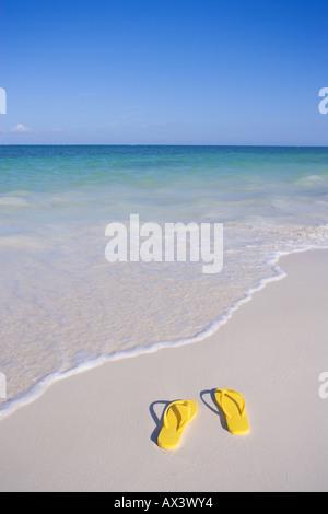 Coppia di giallo flip flop sandals sulla spiaggia al bordo delle acque del Mar dei Caraibi Foto Stock