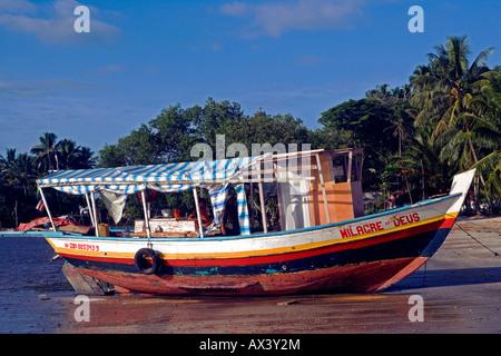 Il Brasile, Bahia, Boipeba isola. Il traghetto collega le isole è ormeggiata sulla spiaggia di fronte palme. Foto Stock