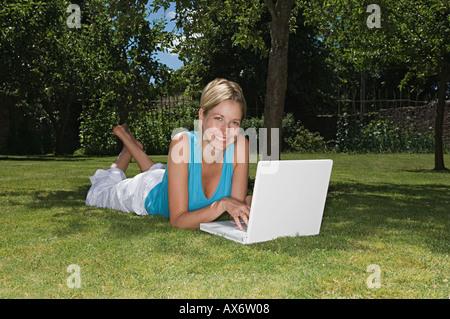 Donna sdraiati sull'erba utilizzando laptop Foto Stock