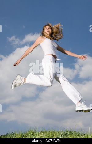Giovane donna jumping a metà in aria Foto Stock