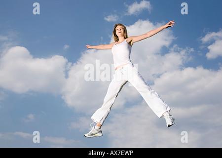 Giovane donna jumping a metà in aria, braccia tese, sorridente Foto Stock
