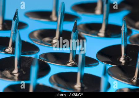 Argento puntine da disegno su sfondo blu Foto Stock