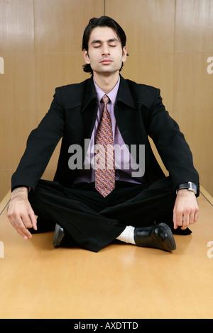 Imprenditore facendo yoga in un ufficio tabella Foto Stock