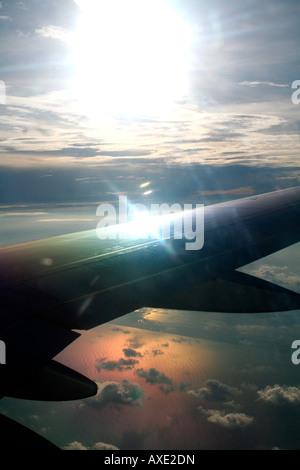 Antenna di overhead bird's-eye-vista della luce del sole che si riflette sull'ala di un velivolo sorvolando un lago Foto Stock