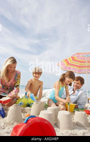 Famiglia giocando in sabbia sulla spiaggia, Maiorca, SPAGNA Foto Stock