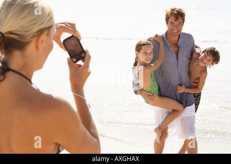 Donna di scattare una foto di mio marito con i bambini sulla spiaggia, Maiorca, SPAGNA Foto Stock