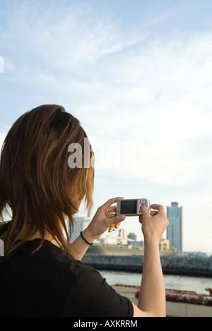 Giovane uomo cityscape di fotografia con la fotocamera digitale, vista posteriore Foto Stock