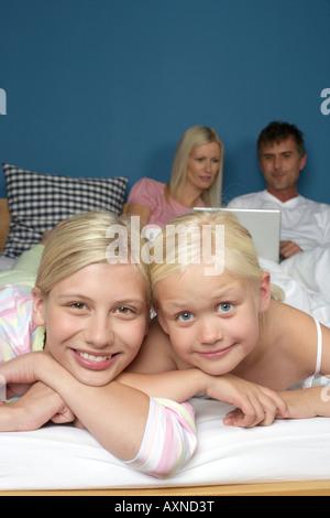 Due ragazze bionda giacente sorridente nel letto dei genitori, il fuoco selettivo, close-up Foto Stock