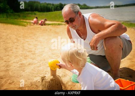 Nonno veglia su nipote sulla spiaggia Foto Stock