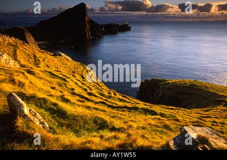 Luce calda del sole al tramonto gettato sul promontorio di curvatura a Neist punto sull'Isola di Skye in Scozia UK Foto Stock