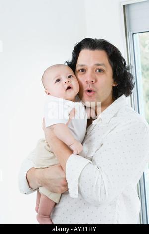 Asian Padre abbracciando baby Foto Stock