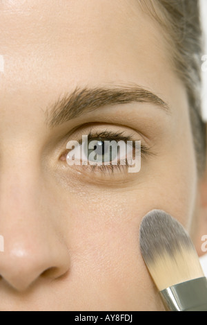 Donna di applicare il make-up a guancia, vista ritagliata della faccia Foto Stock